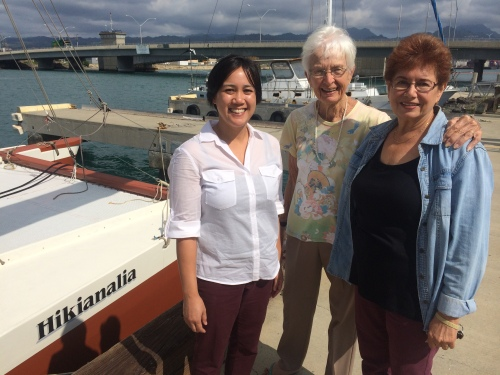 Head Archivist Janel Quirante, Laura Thompson and PVS Manager Ramona Ontiveros in front of the Hikianalia which will escort the Hokuleʻa on its sail. Photo by: Heather Giugni.